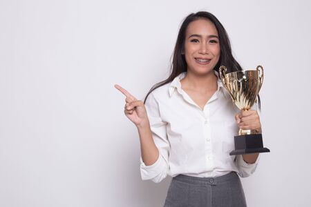 Successful young asian woman holding a trophy point to blank space on white background Фото со стока