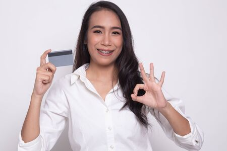 Young Asian woman show OK with a blank card on white background