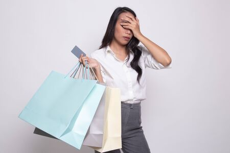 Unhappy  young Asian woman with shopping bags and credit card on white background Фото со стока