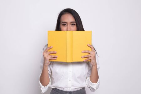 Young Asian woman with a book cover her face on white background