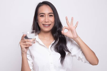 Young Asian woman show OK with a glass of drinking water on white background Stock Photo
