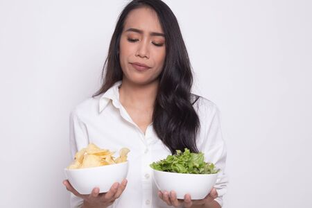 Young Asian woman with potato chips and salad on white background