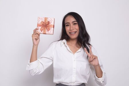 Asian woman show victory sign with a gift box on white background 写真素材