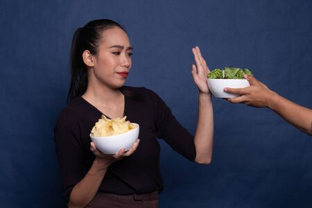 Young Asian woman with potato chips say no to salad on blue background