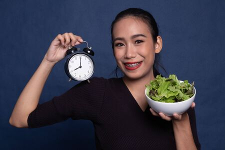 Young Asian woman with clock and salad on blue background Stock Photo