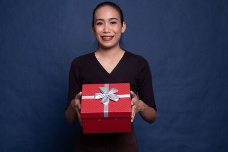 Asian woman thumbs up with a gift box on blue background