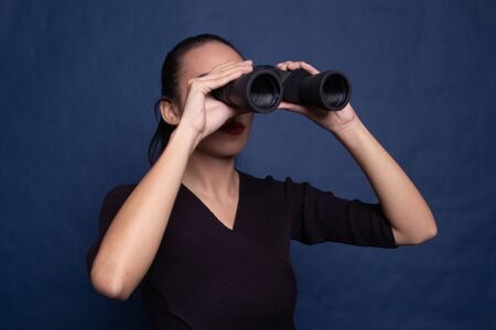 Young Asian woman with binoculars on blue background