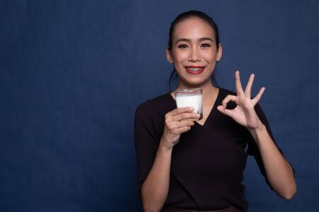 Healthy Asian woman drinking a glass of milk show OK sign on blue background