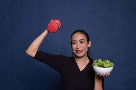 Healthy Asian woman with dumbbells and salad on blue background