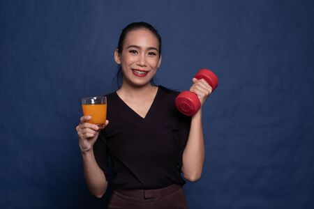 Young Asian woman with dumbbell drink orange juice on blue background