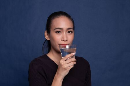 Young Asian woman with a glass of drinking water on blue background