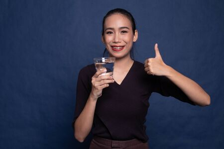 Young Asian woman thumbs up with a glass of drinking water on blue background