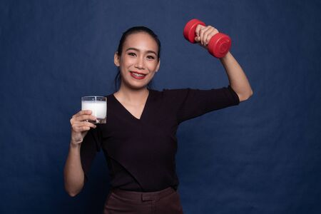 Healthy Asian woman drinking a glass of milk and dumbbell on blue background Stock Photo