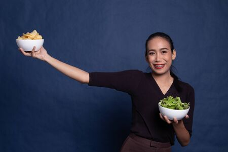 Young Asian woman with potato chips and salad on blue background