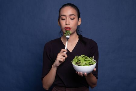 Healthy Asian woman with salad on blue background Stock Photo