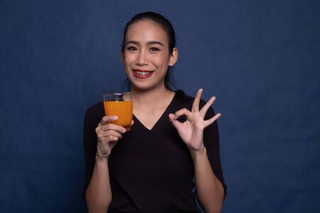 Young Asian woman drink orange juice show OK sign on blue background