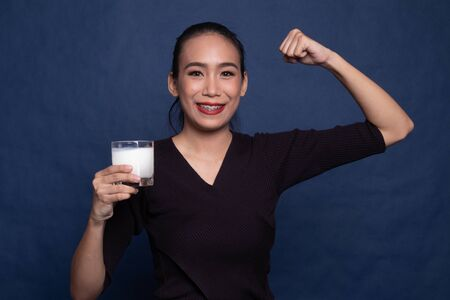 Healthy Asian woman drinking a glass of milk on blue background