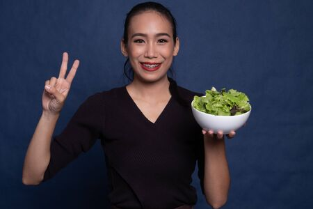Healthy Asian woman show victory sign with salad on blue background