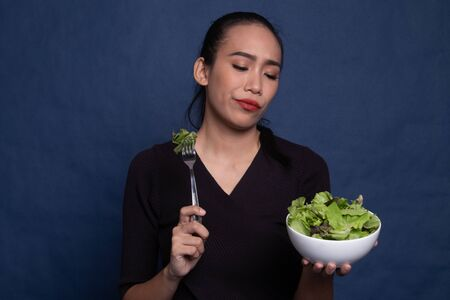 Asian woman hate salad on blue background