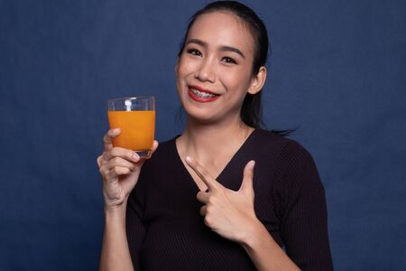 Young Asian woman point to orange juice on blue background Stock Photo