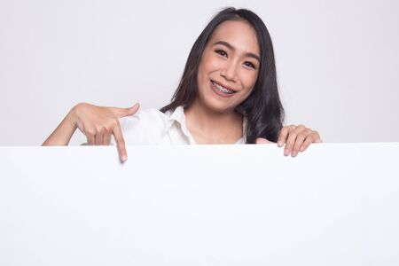 Young Asian woman point to a  blank sign on white background