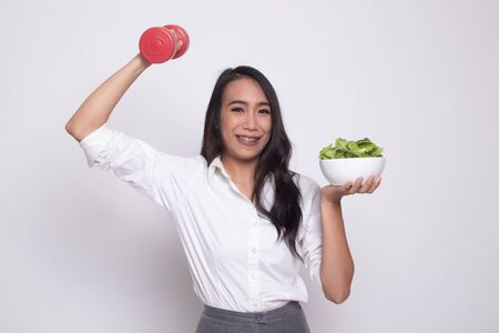Healthy Asian woman with dumbbells and salad on white background