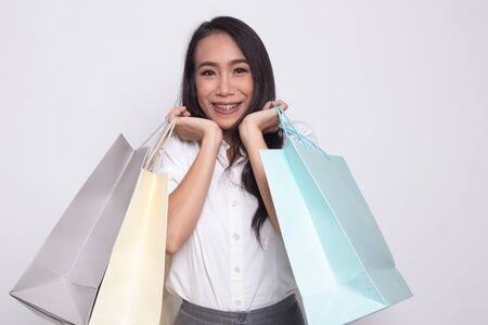 Beautiful young Asian woman with shopping bags on white background