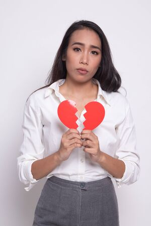 Beautiful young Asian woman with broken heart on white background Reklamní fotografie