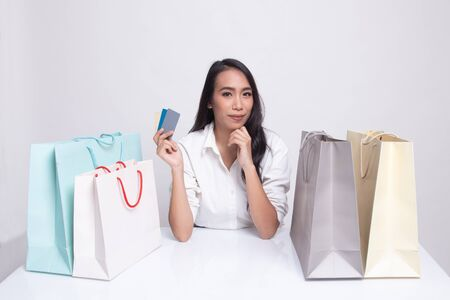 Young Asian woman with shopping bag and blank card on white background Reklamní fotografie