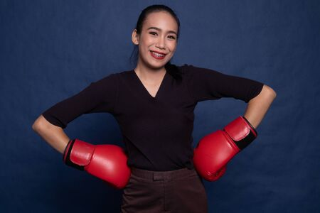 Young Asian woman with red boxing gloves on blue background Stock Photo