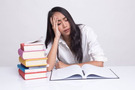Exhausted Young Asian woman read a book with books on table on white background Stok Fotoğraf