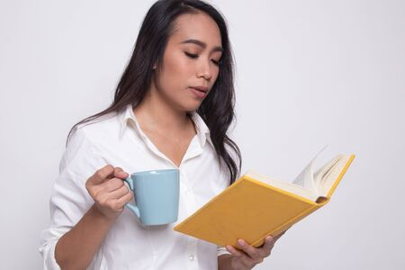 Young Asian woman with a book and cup of coffee on white background Stok Fotoğraf