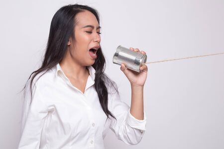 Young Asian woman shout with tin can phone on white background