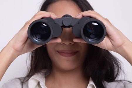 Joven mujer asiática con binoculares sobre fondo blanco.