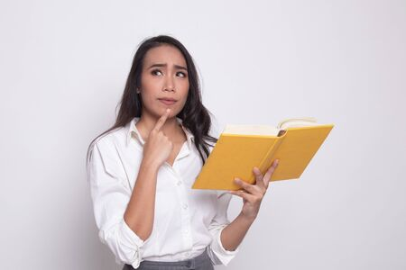 Young Asian woman with a book is thinking on white background