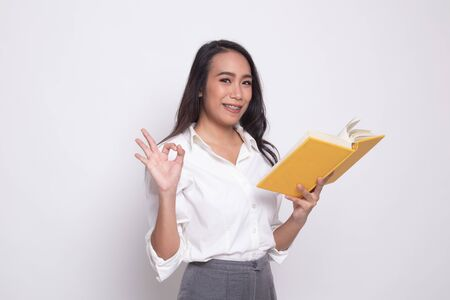 Young Asian woman show OK with a book on white background