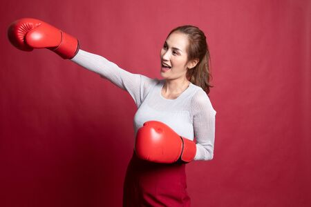 Young Asian woman with red boxing gloves on red background