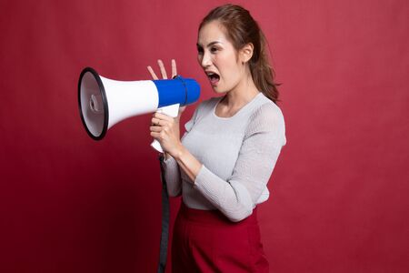 Beautiful young Asian woman announcer with megaphone on red background