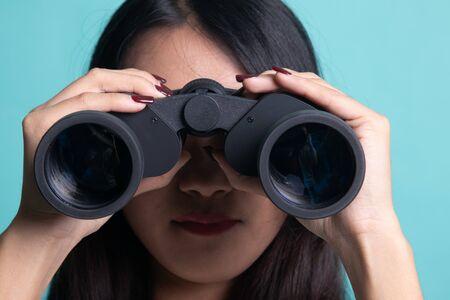 Young Asian woman with binoculars