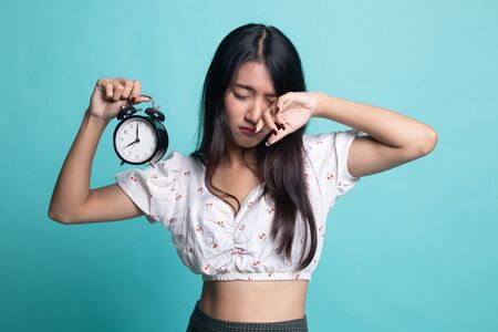 Sleepy young Asian woman with a clock in the morning on cyan color background