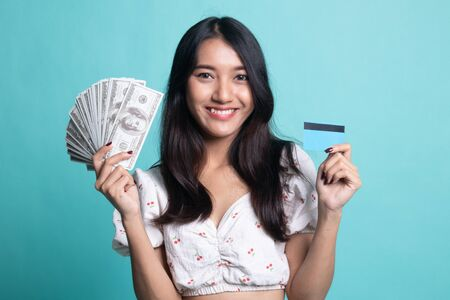 Portrait of young asian woman showing bunch of money banknotes on cyan color background Zdjęcie Seryjne