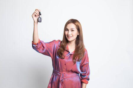 Cute asian girl showing home residence keys on white background 免版税图像
