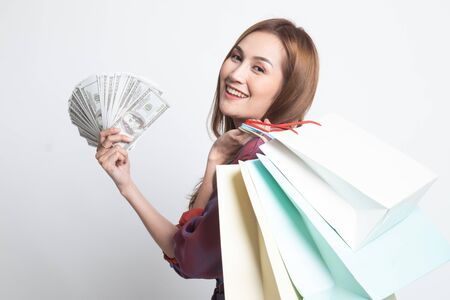 Portrait of young asian woman showing bunch of money banknotes on white background