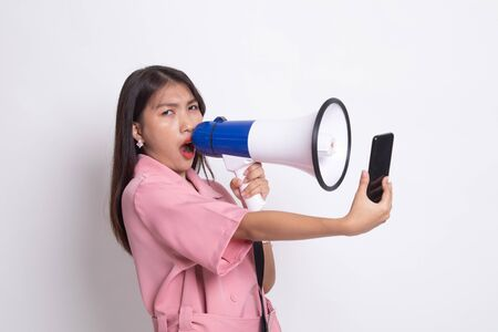 Angry  young Asian woman shout with megaphone to mobile phone on white background.