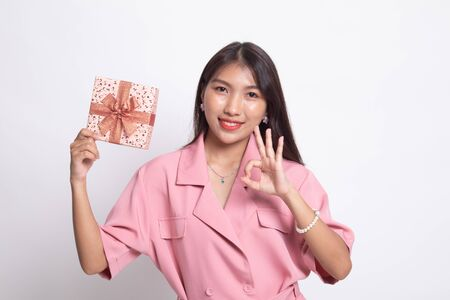 Young Asian woman show OK with a gift box on white background.