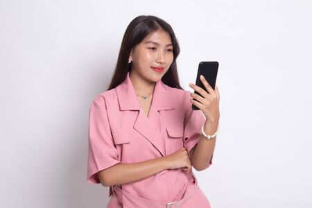 Young Asian woman with mobile phone on white background.