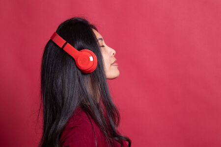 Pretty asian girl listening music with her headphones on red background.