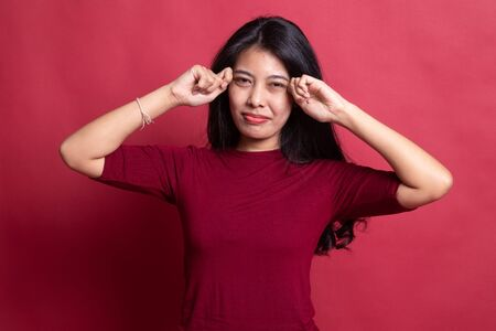 Young Asian woman sad and cry on red background.