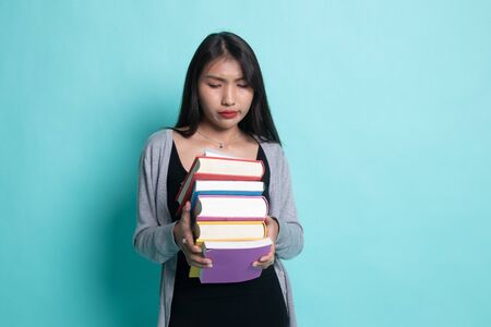 Unhappy young Asian woman studying  with may books on cyan background.