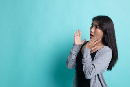 Beautiful young Asian woman shocked  and look up on cyan background.